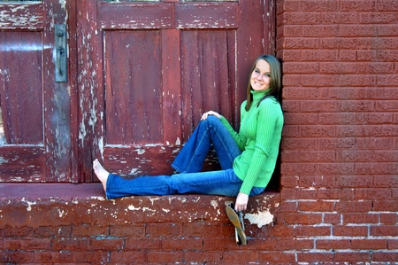 Attractive young woman sits in front of alley doorway   Paint is peeling and cracked   She is wearing jeans and is barefoot  photo
