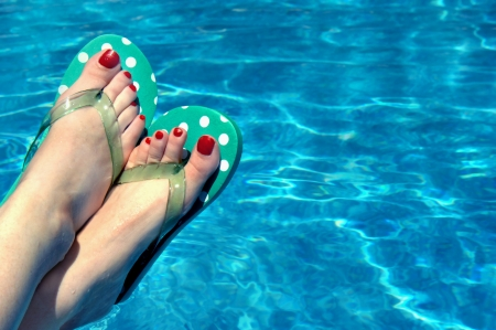 Female relaxes besides swimming pool   Corner image shows only her feet clad in flip flops and red toe nails   Water shimmers in background