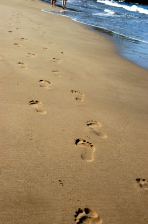 Footprints form disappearing path as couple walk along a beach on the island of Kauai, Hawaii.