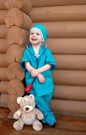 aspiring: Little boy wears a scrub suit and stands besides his first patient a teddy bear wearing a bandaged arm.