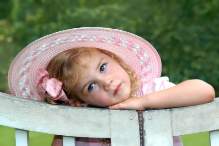 Lost in thought, beautiful little girl leans her head on a white wooden gate   She is wearing a pink dress, pearls and wide brimmed hat Stock Photo - 16304420