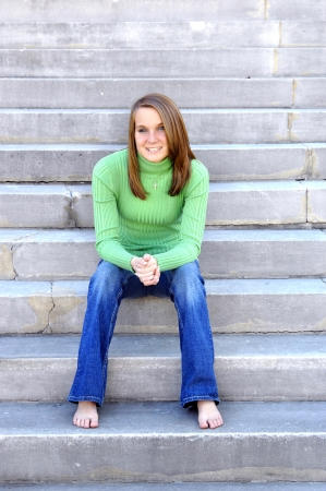 Attractive young woman relaxes on concrete steps   She is wearing jeans and is barefoot   She is smiling and happy  photo