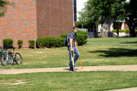 College student struggles to get across campus on crutches   He is carrying a backpack on his back  photo