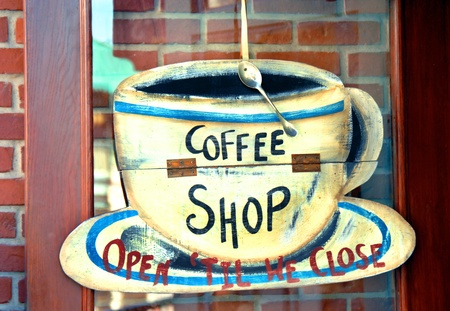 Humorous coffee shop sign is attached to cafe entry.  Spoon is attached to coffee cup on saucer.