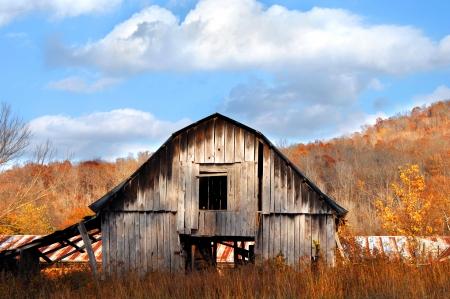Ozark bergen vormen achtergrond voor rustiek en verweerde schuur in het noorden van Arkansas. Kleurrijke herfst gebladerte en blauwe luchten maken het levendig met kleuren.