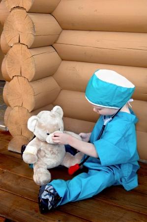 doctoring: Little boy finge di fissare il suo orsacchiotto mentre vestita in macchia di un chirurgo.