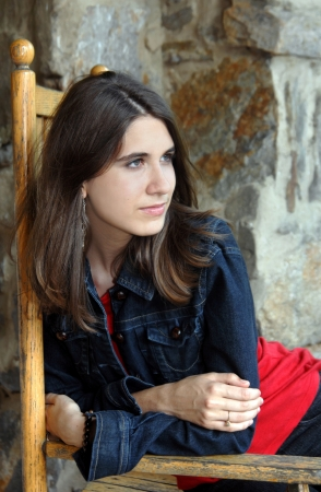 Young woman relaxes in wooden rocking chair.  She is wearing a denim jacket and red shirt. photo