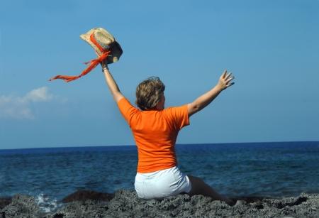 Oudere vrouw zit op zwarte lava rotsen op de ruige kustlijn van de Kona kust van de Big Island van Hawaï. Ze zwaait haar strooien hoed en oranje sjaal Inde lucht.
