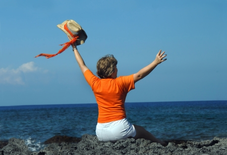 Older woman sits on black lava rocks on the rugged coastline of the Kona Coast of the Big Island of Hawaii.  She is waving her straw hat and orange scarf inthe air.