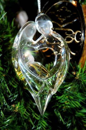 mother of jesus: Chrystal ornament depicts Mary and Joseph holding baby Jesus.  Light glows through ornament as it hangs on the branches of a Christmas tree.