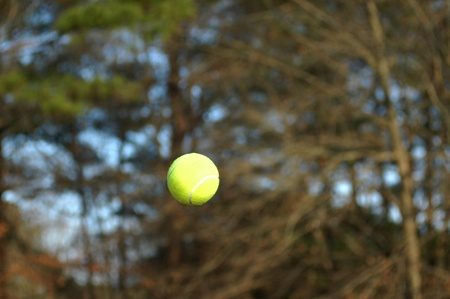 Tennis ball flies through the air during a tennis match.  Flight is captured and ball is frozen in mid air.
