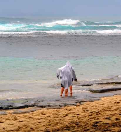 It rains in paradise, too!  Two tourists cover with towels and explore the wet beach and waves.