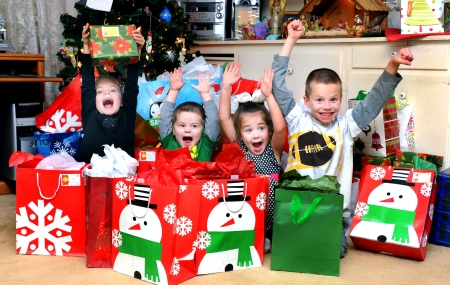 Four children sit surrounded by Christmas packages   It is Christmas morning and their excitement is overflowing   There are two girls and two boys and they scream with joy  photo