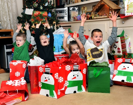 Four children express their Christmas joy and excitement by raising their arms and yelling  merry christmas    They are posing in front of the Christmas tree covered up in gifts  photo