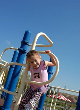 playground equipment: Little girl climbs through a metal hoop on playground equipment   She is smiling and happy   Equipment is blue and white