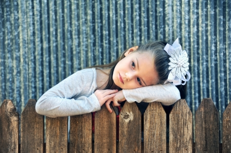 lost in thought: Little girl rests her head on her arms along a rustic wooden fence.  She has on a large white hairbow and grey shirt.  She lost in thought and day dreaming.