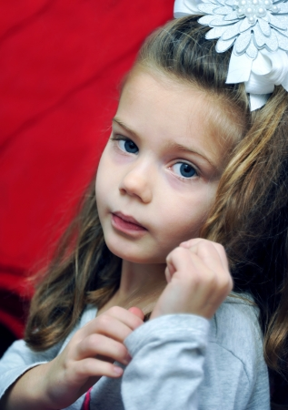 lost in thought: Little girl is lost in thought.  She has blue eyes and is wearing a white hairbow.