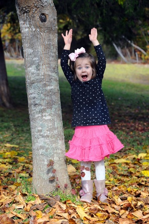 Little girl leaps for joy as she plays in the Autumn leaves in Arkansas.  She has on a black polka dot top and hot pink skirt. photo