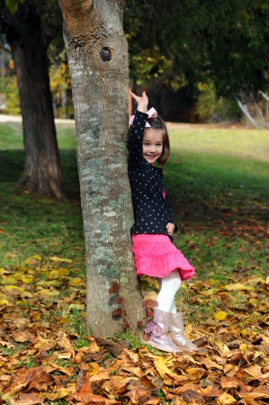 Little girl waves hello or goodbye as she stands besides a tree surrounded by Autumn leaves.  She is wearing a pink skirt and black top.  Her smile is big. photo