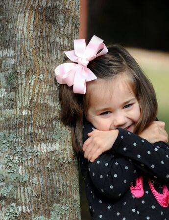 Bursting with happiness, little girl hugs herself as she leans against a tree.  She is wearing a pink hairbow and black shirt. photo
