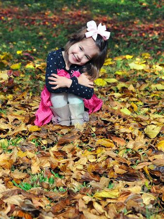 Bursting with joy, little girl hugs her knees and beams a smile.  She is playing in the golden leaves of Fall on an Arkansas afternoon. photo