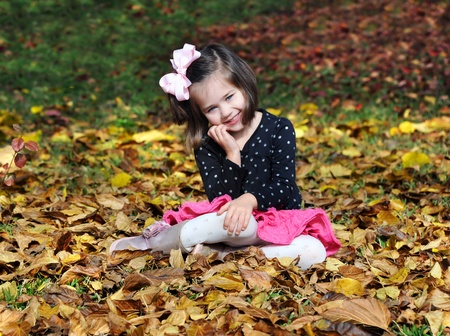 Beautiful little girl plays in the Fall leaves.  She is sitting and smiling happily.  Yellow leaves surround her. 写真素材