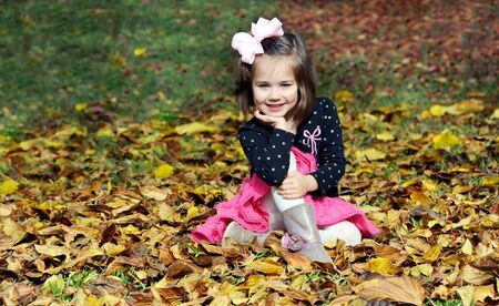Impish little girl pauses to smile while playing in the leaves on an Autumn afternoon.  She is surrounded by yellow leaves. photo