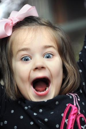 小さな女の子のクローズ アップの写真に喜びの悲鳴します。彼女はピンク hairbow と黒水玉ドットのシャツを着てください。彼女の口が広く開いてい 写真素材