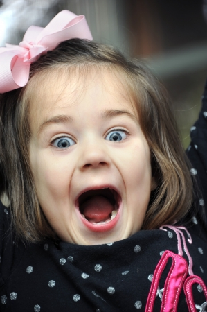 Little girl screams for joy in a closeup photo.  She is wearing a pink hairbow and black polka dotted shirt.  Her mouth is wide open and her eyes sparkle. Imagens