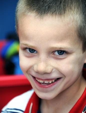 """chłopięctwo: ChÅ'opiec uÅ›miecha siÄ™ gÅ'upkowato do kamery. Zbliżenie pokazuje swoje piegi i nowe zÄ™by. Urok dzieciÅ""""stwa emanuje z jego nieÅ›miaÅ'ych oczach. Zdjęcie Seryjne"""