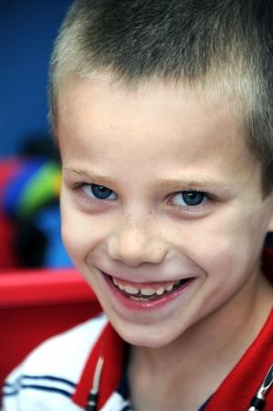 chłopięctwo: Chłopiec uśmiecha się głupkowato do kamery. Zbliżenie pokazuje swoje piegi i nowe zęby. Urok dzieciństwa emanuje z jego nieśmiałych oczach.