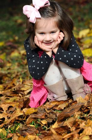 crouches: Playful and sweet, little girl crouches in the leaves during playtime.  She is smiling and happy wearing a pink hairbow, pink skirt and black polka dotted top. Stock Photo