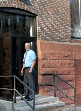 Professor pauses at entry to classroom on college campus in Michigan.  He is wearing a blue shirt and dark slacks.  He is standing on top step with door open. Stock Photo - 16969624