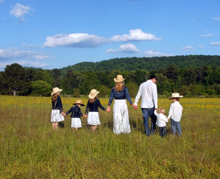 Mom and Dad lead children across open field of yellow flowers in rural Alabama photo