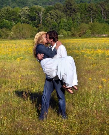 Echtpaar genieten van romantisch moment in het veld van gele bloemen