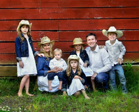 Family of seven pose besides red, wooden barn