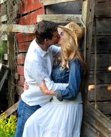 countryside loving: Couple share a romantic kiss leaning against a rustic, red wooden barn