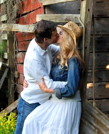 Koppel delen een romantische kus leunend tegen een rustieke, rode houten schuur