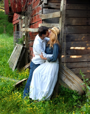 Couple enjoy a romantic kiss against a rustic and secluded setting