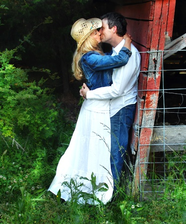 Young couple embrace behind the barn. photo