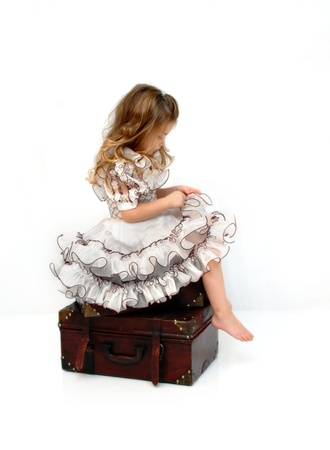 Gorgeous little girl sits on a stack of wooden suitcases Stock Photo - 17082572