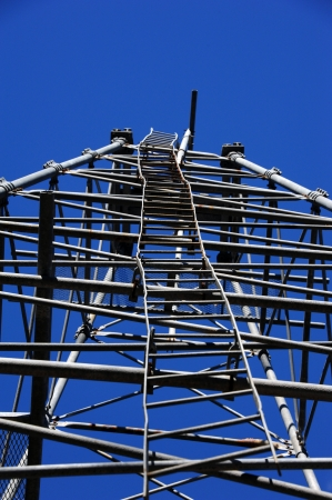 Crooked, bent ladder ascends into the sky.  Ladder is attached to metal oil derrick at the Arkansas Museum of Natural Resources in El Dorado, Arkansas.