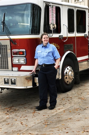 leaning on the truck: Attractive woman fire fighter stands in blue uniform besides fire truck in Arkansas.  She is looking at camera and is smiling.