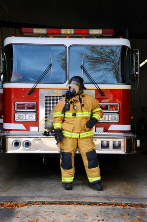 suited up: Woman firefighter stands in front of fire truck at fire station.  She is wearing bunking gear complete with gas mask and helmet.