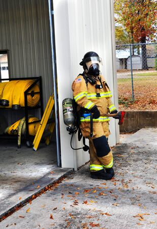 suited up: Fire Woman stands holding flat head axe as she leans against fire station.  She is suited up in her Bunking Gear and is ready for any fire emergency. Stock Photo