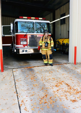 fire station: Young woman stands in front of firetruck at fire station.  Fire woman is suited up in bunking gear and holds a flat head axe.