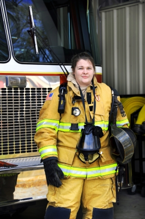 Attractive female firefighter stands in front of fire truck.  She is holding her helmet and gas mask hangs around her neck.