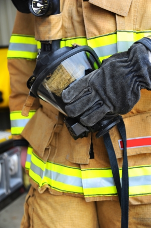 face mask: Fireman holds gas mask in his gloved hand.  Mask is black with straps and protective netting.