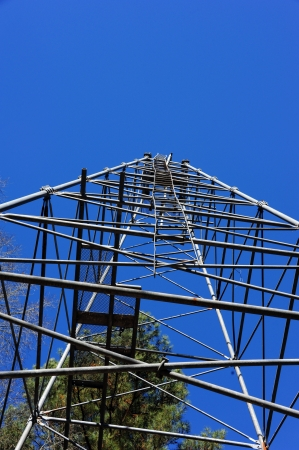 oil derrick: Oil derrick iron frame crawls into a vivid blue sky   Ladder is broken and crooked