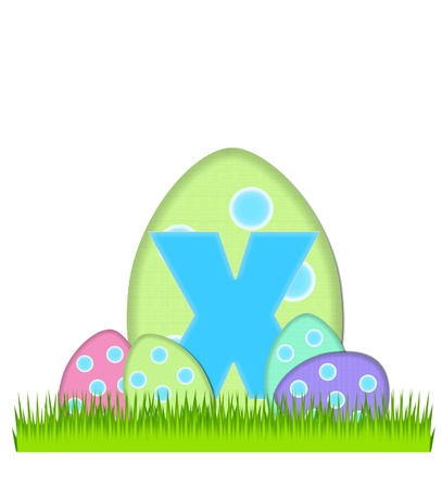 The letter X, in the alphabet set Big Egg Hunt, is soft aqua.  Letter sits on big Easter egg that is decorated with polka dots.  Smaller eggs sit in grass at base of hidden egg. photo